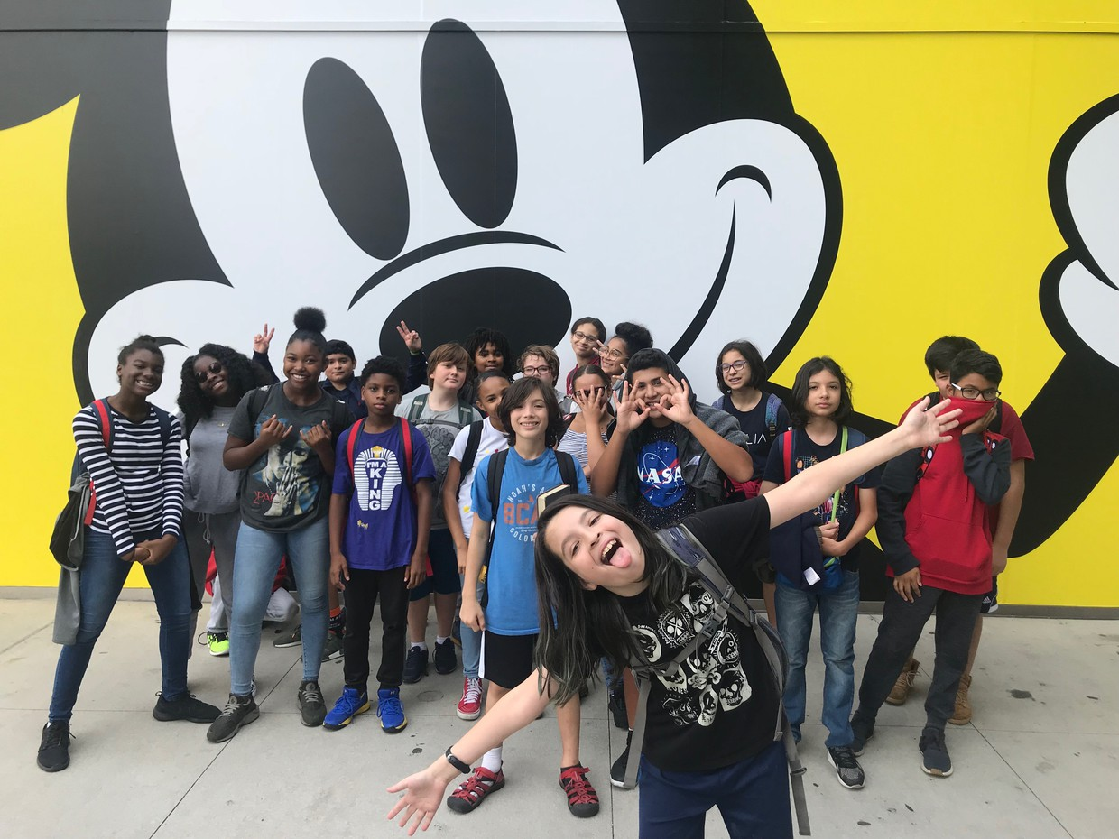 students in front of a mural